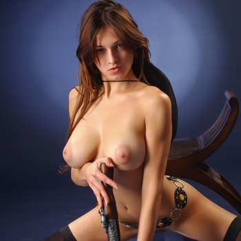 Hot chick with big boobs holds a musket at erotic photoshoot