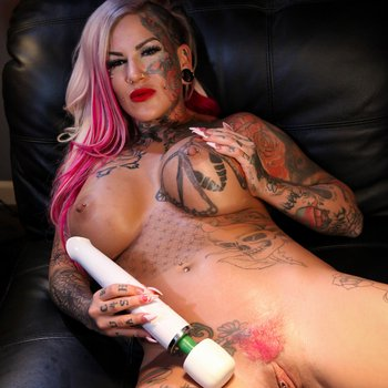 Busty Evilyn Ink using a vibrator on her pussy