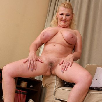 Kira T on a couch spreading pussy showing jugs