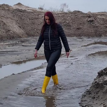 Red haired MILF walks in mud wearing rubber boots