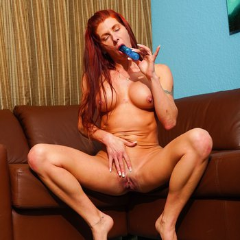 Redhead nympho with round tits plays with a dildo