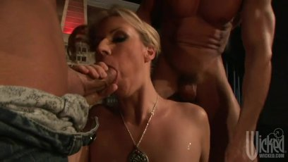 Busty blonde Carolyn Reese gets two big cocks jammed in her slutty mouth