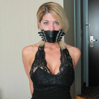 Gorgeous blonde in a black lace top and a gag