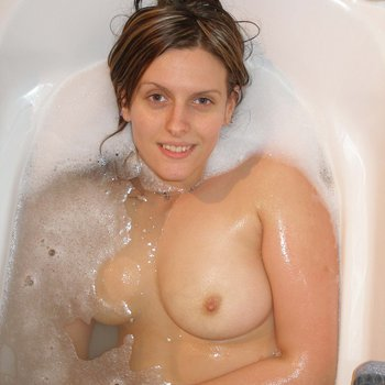 Brunette babe in the tub getting tits soaked