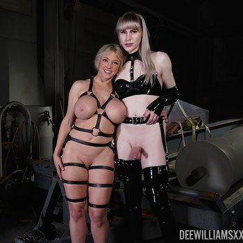 Thick MILF Dee Williams poses with a shemale friend wearing leather garters